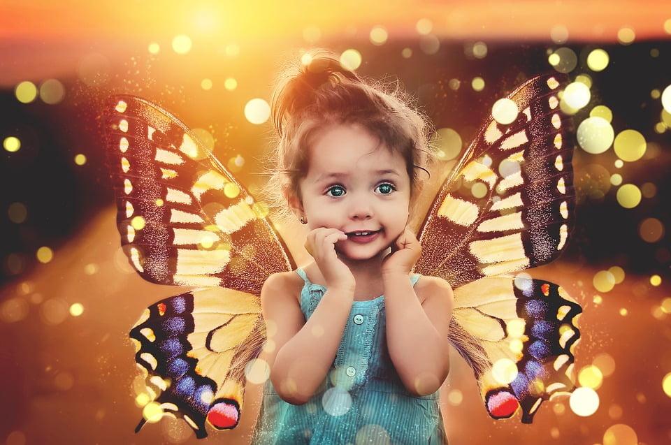 На фото изображена девочка с крыльями бабочки