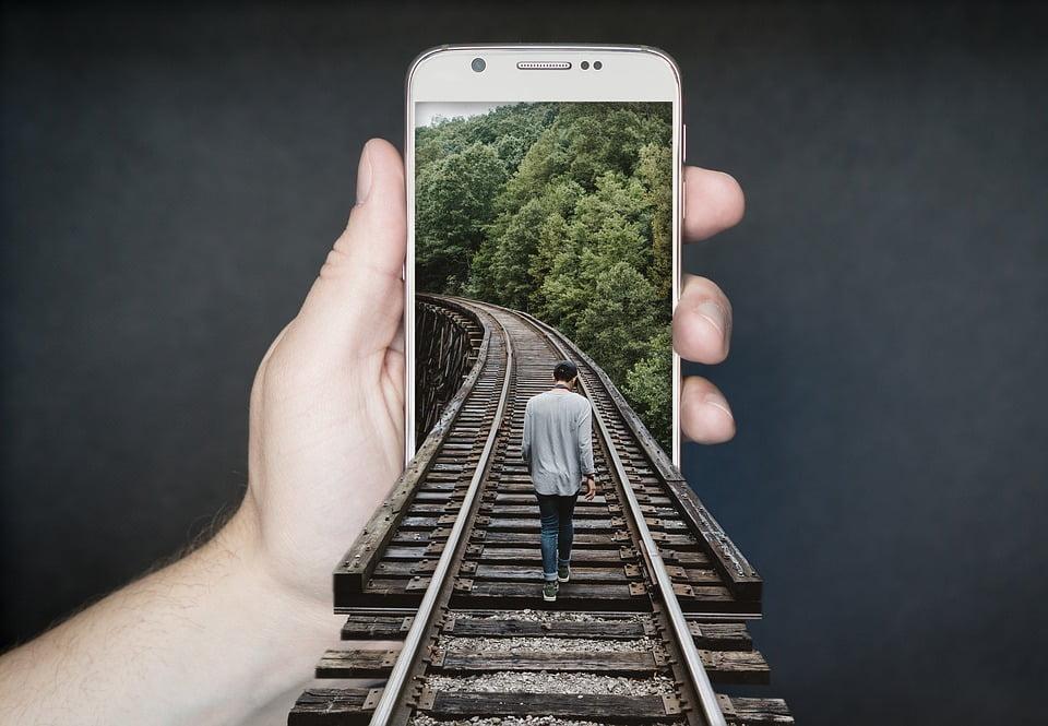 На фото изображен мужина, идущий по железной дороге