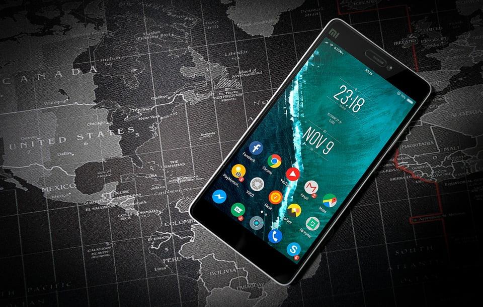 На фото изображен телефон на карте мира