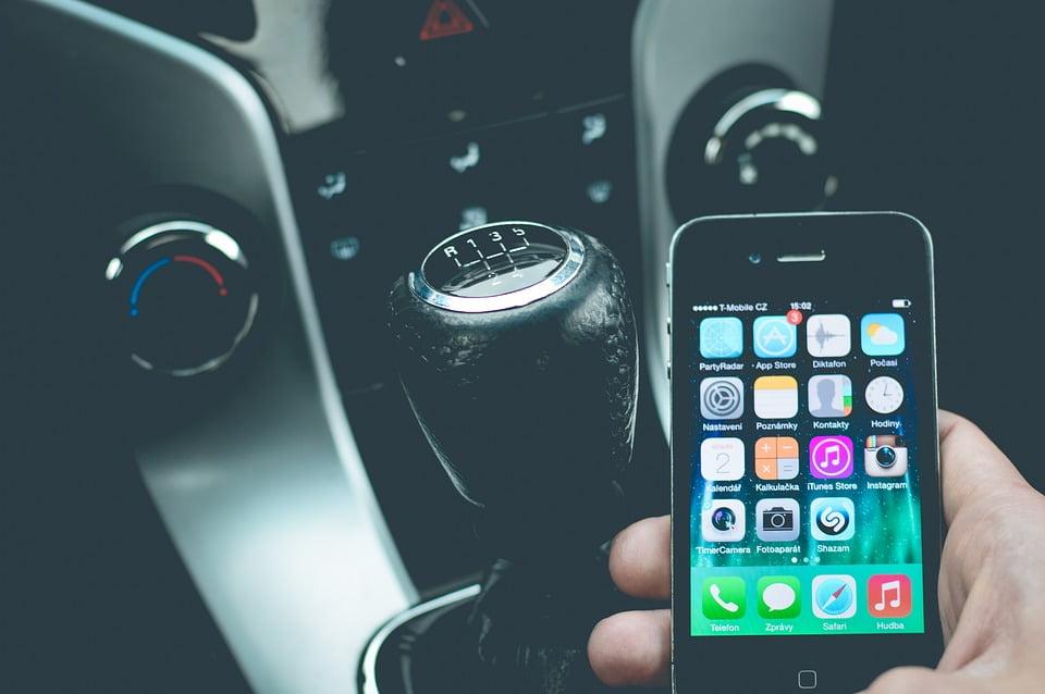 На фото изображена ручка коробки передач и мобильный телефон