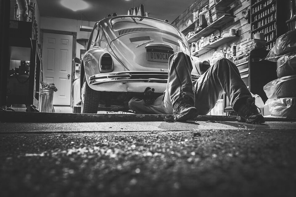 На фото изображено как мужчина ремонтирует машину.