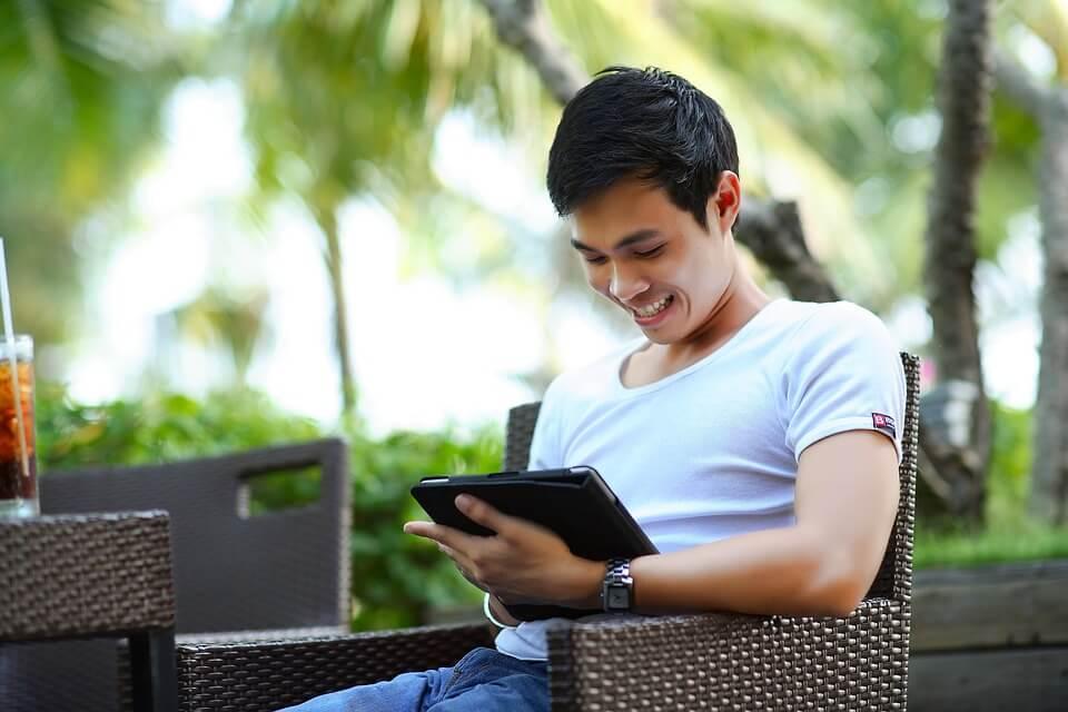 На фото изображен парень, сидящий в кресле с планшетом в руках.