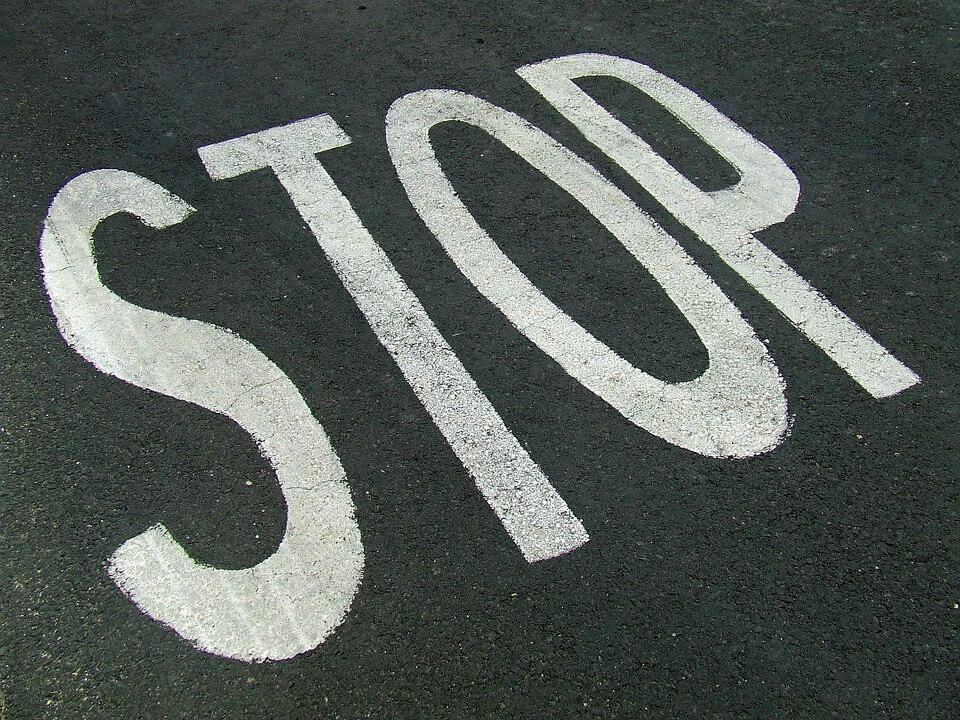 На фото изображена надпись STOP на асфальте.
