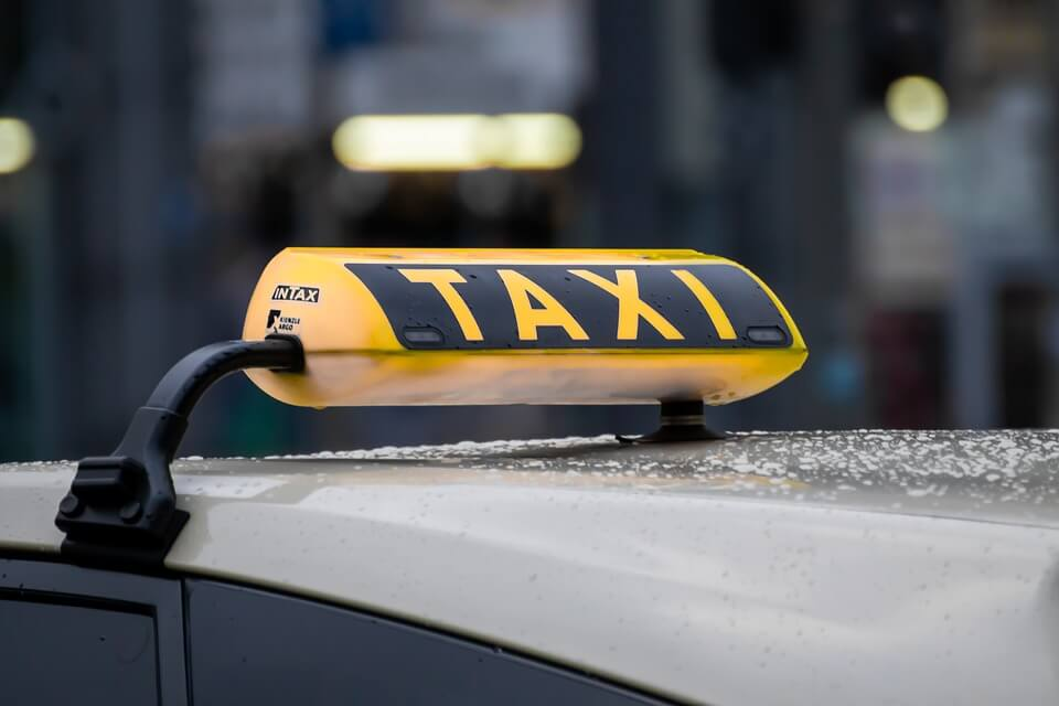 На фото изображена шашка такси на крыше машины.