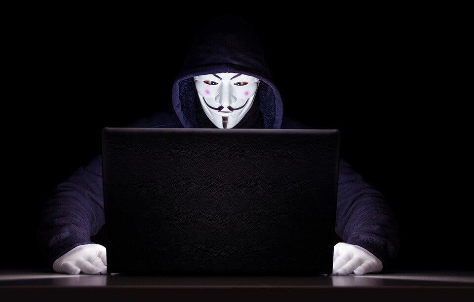 На фото изображен компьютерный шпион в маске.