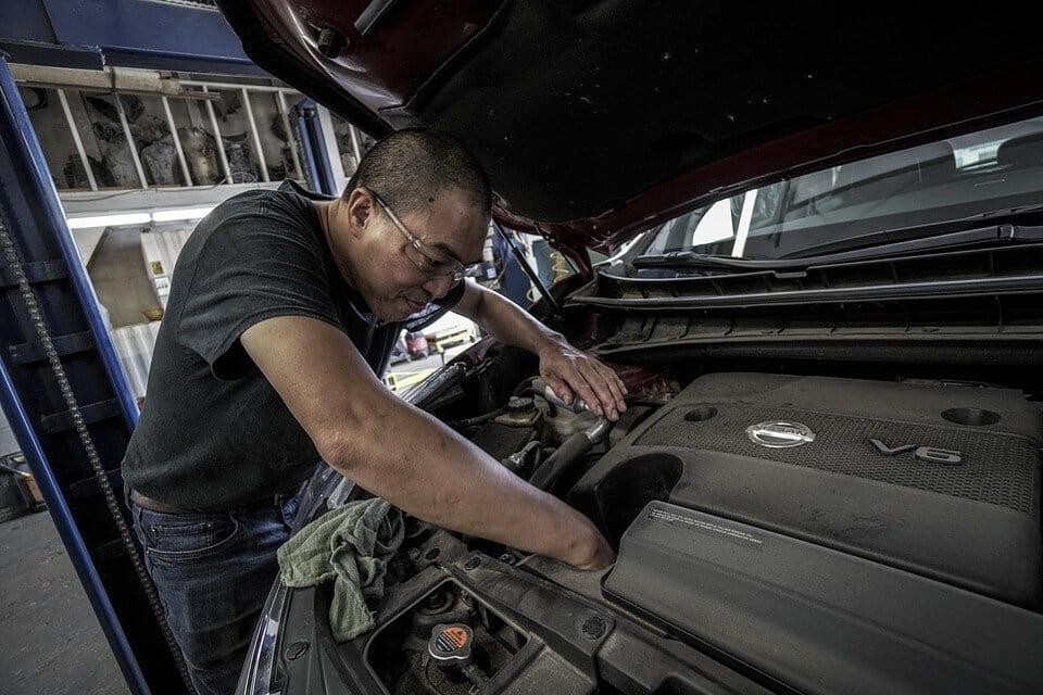 На фото изображено как мужчина ремонтирует автомобиль.