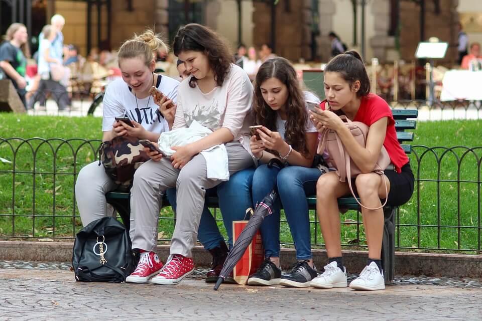 На фото изображена компания девочек подростков с телефонами в руках.