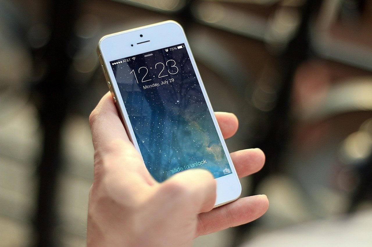 На фото изображен телефон в руках владельца.