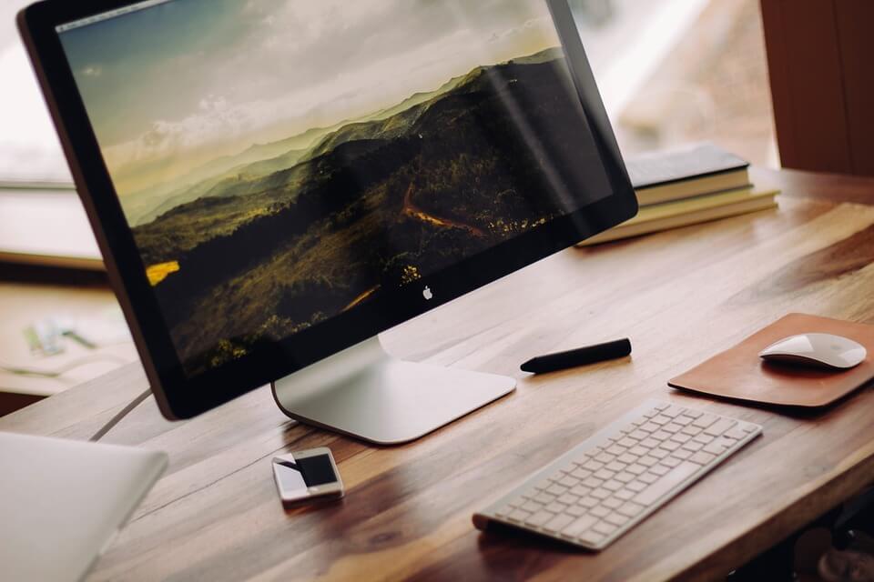 На фото изображен монитор компьтера и клавиатура, которые стоят на столе.