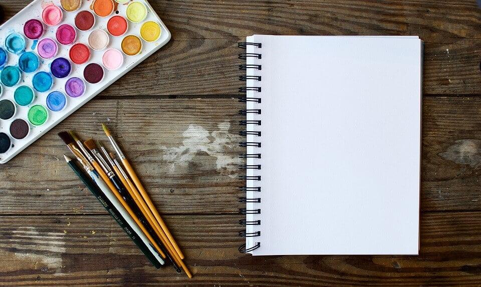 На фото изображен блокнот, кисти и краски для рисования.