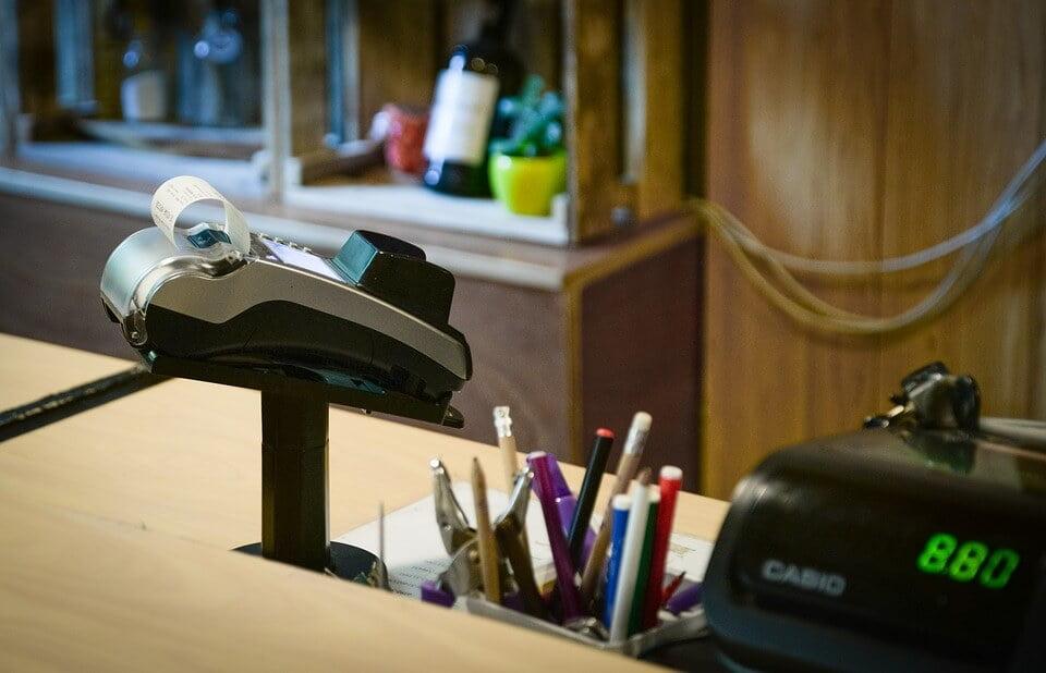 На фото изображен терминал для оплаты с чеком, который стоит на столе у кассового аппарата.