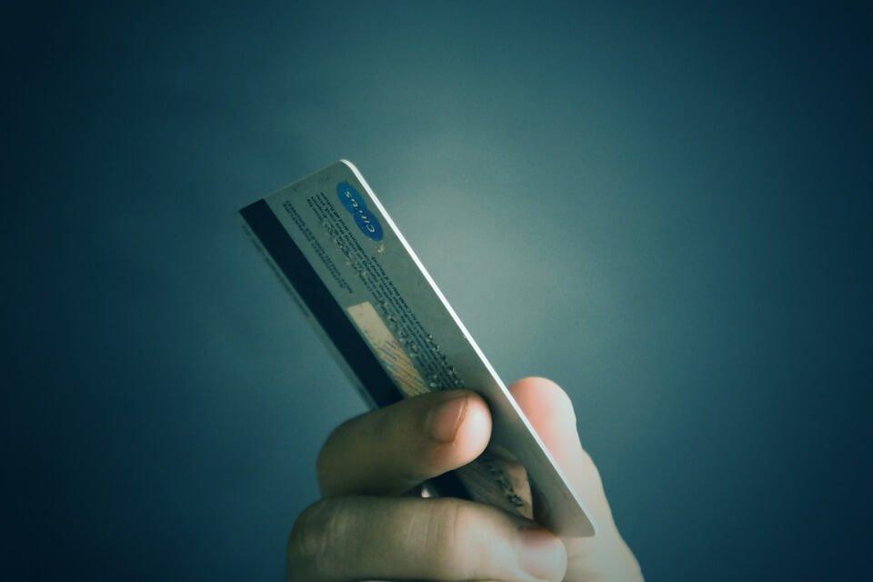 На фото изображена кредитная карта в руке.