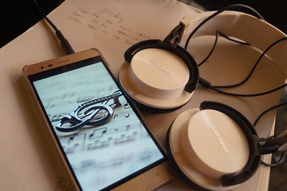 На фото изображены наушники, подключенные к смартфону, на экране которого изображен скрипичный ключ.