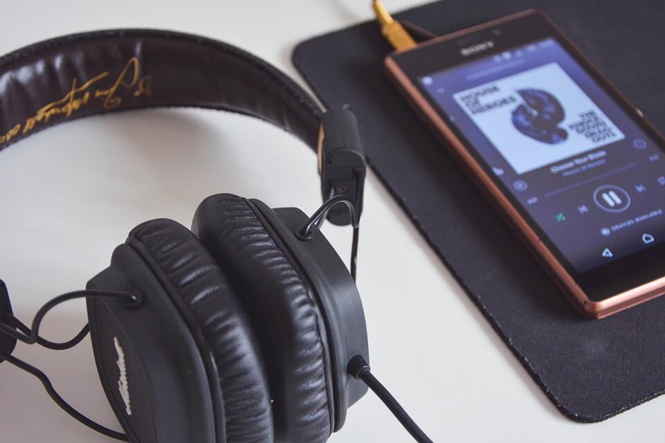 На фото изображен телефон, на котором играет музыка и наушники.