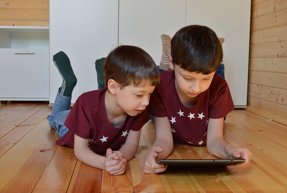 На фото изображены дети, которые смотрят что-то на планшете, лежа на полу.