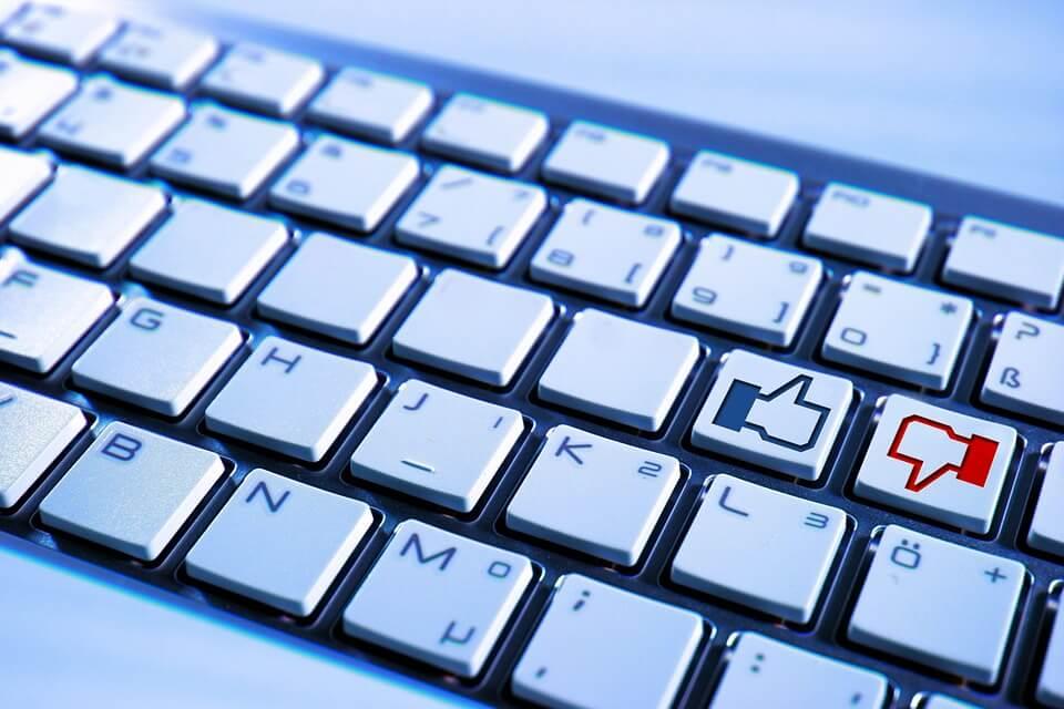 На фото изображена компьютерная клавиатура, на кнопках которых изображены лайк и дизлайк.