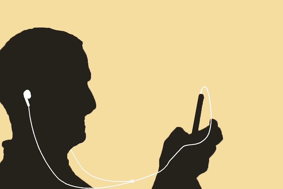 На фото изображено как человек слушает музыку на телефоне через наушники.