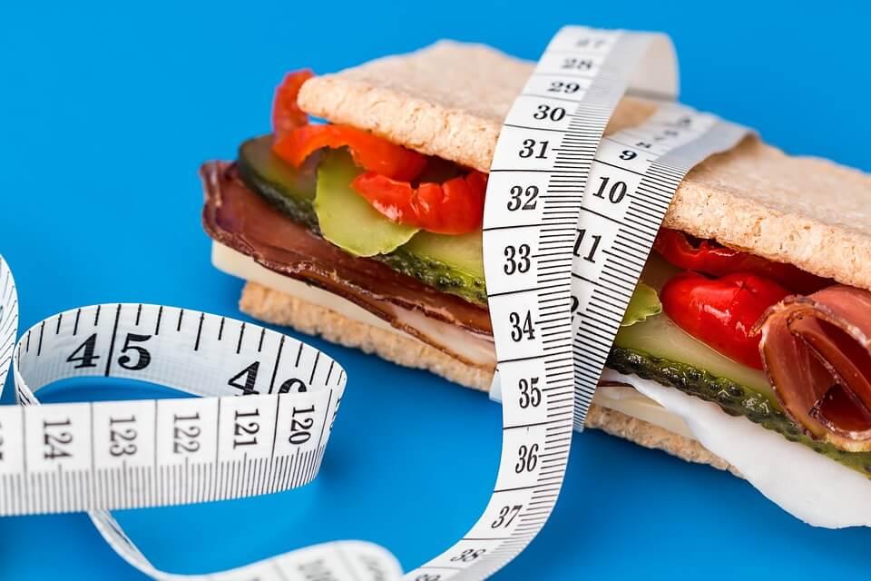 На фото изображен сендвич, обмотанный сантиметром.