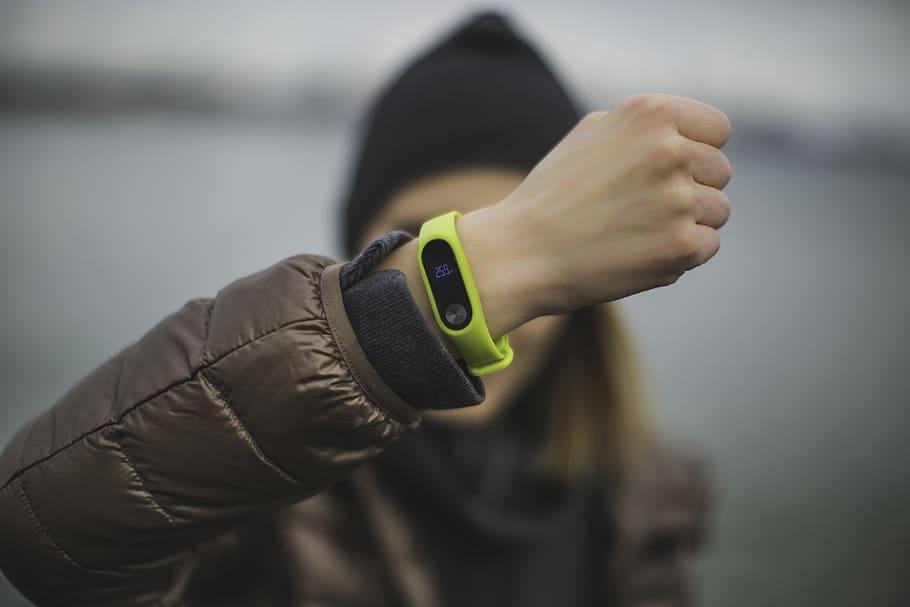 На фото изображен фитнес-браслет на руке девушки.