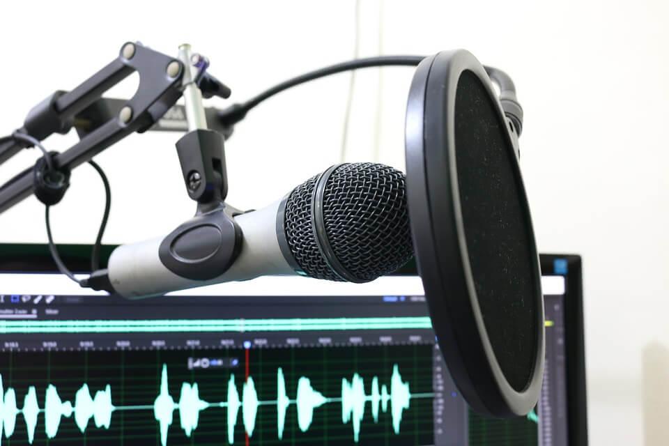 На фото изображен микрофон и экран компьютера со звуковыми волнами.