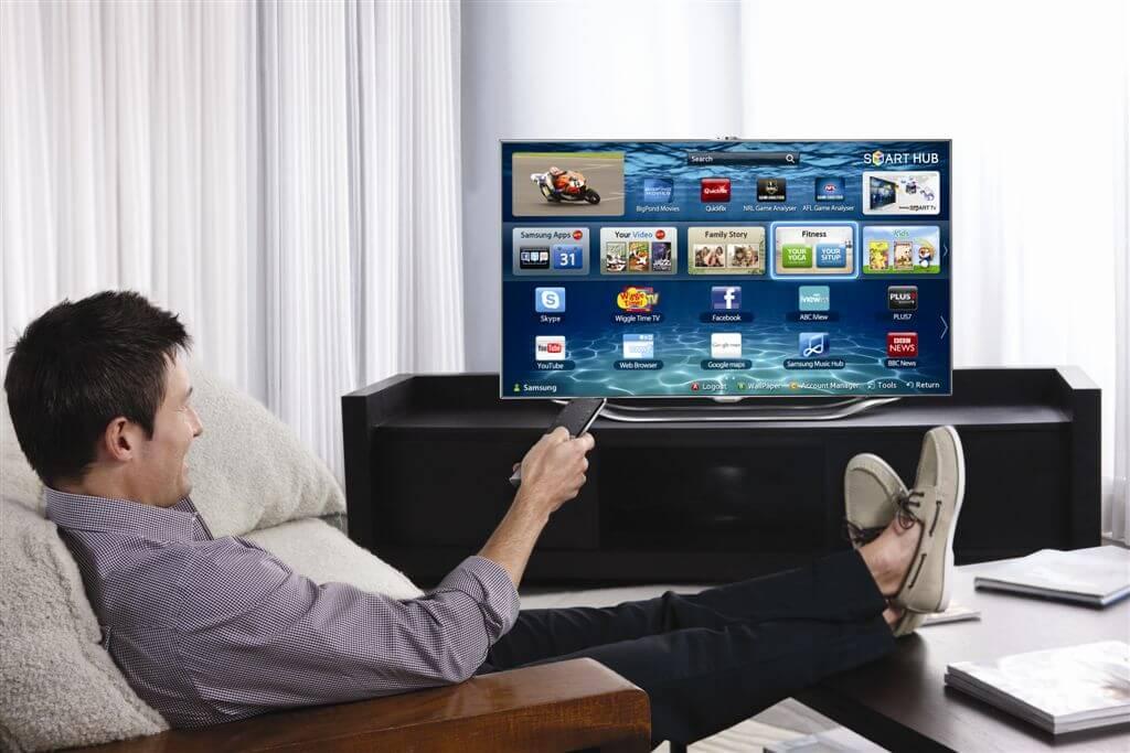 На фото изображен мужчина, который сидит перед телевизором с пультом.